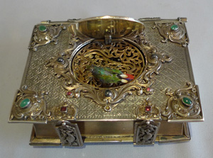 Singing bird box in form of a jewelled book in silver with enamel hand painting.