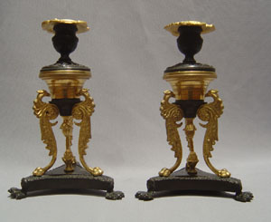 Antique pair of English Regency patinated bronze and ormolu candlesticks.