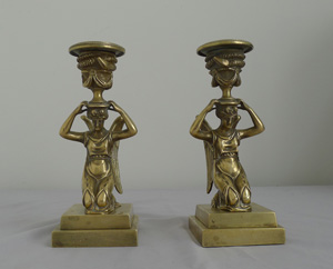 Antique pair of English bronze candlesticks of kneeling winged figures.
